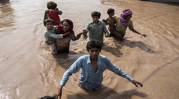 Flood victims wade through a flooded field in Kashmir. Reuters photo.