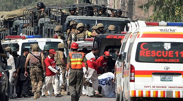 Pakistani soldiers arrive to take position as volunteers move an injured person outside a Pakistan Air Force base after an attack by militants in Peshawar on September 18, 2015. Militants attacked a Pakistani air force base near the northwestern city of Peshawar, the military said, adding that at least six attackers had been killed and 10 soldiers injured. AFP PHOTO / A MAJEED