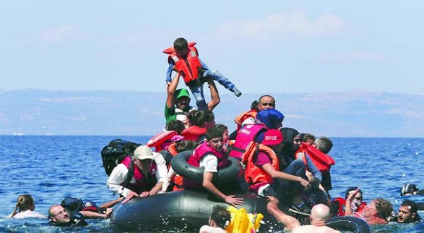 A refugee raises a child into the air as the dinghy they are riding deflated some 100 meters away before reaching the Greek island of Lesbos, on Sunday. (Reuters)